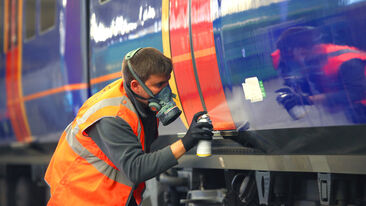 Man in PPE sprays train for installation for Aura Brand Solution