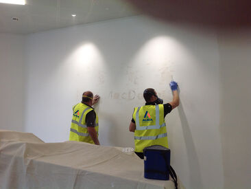 Team carrying out surface repairs, preparation and paint for new signage to wall