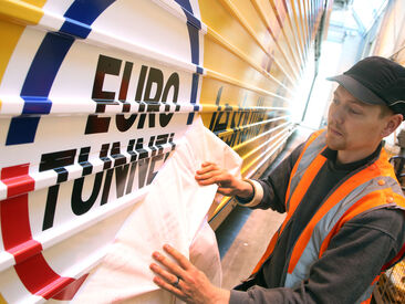 Man applying the euro tunnel logo onto the carriage exterior