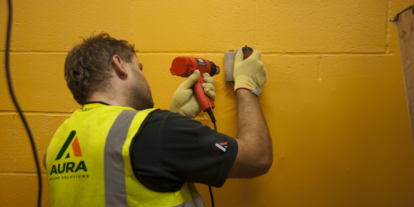 Installation of printed textured wall film on to block wall at Wolves football stadium
